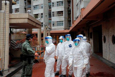 Polizisten in Schutzanzügen beginnen mit der Evakuierung eines Hauses in Hongkong.